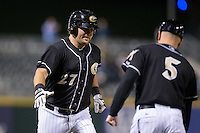 Dan Black (27) of the Charlotte Knights slaps hands with third base coach Ryan Newman (5) after hitting a game tying home run in the bottom of the 9th inning against the Toledo Mud Hens at BB&T BallPark on April 27, 2015 in Charlotte, North Carolina.  The Knights defeated the Mud Hens 7-6 in 10 innings.   (Brian Westerholt/Four Seam Images)