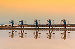 Salt workers start their shift early in golden light at sunrise by Lam Nghiem