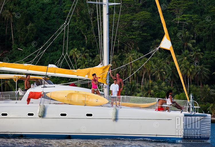 Tahitian spectators aboard catamaran at sailboat race