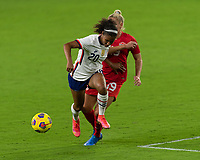 ORLANDO CITY, FL - FEBRUARY 18: Margaret Purce #20 dribbles away from Adriana Leon #19 during a game between Canada and USWNT at Exploria stadium on February 18, 2021 in Orlando City, Florida.