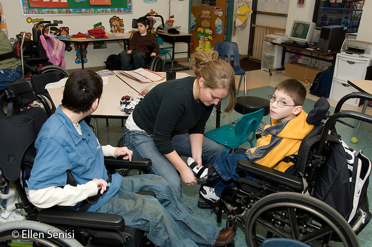 MR / Albany, NY.Langan School at Center for Disability Services .Ungraded private school which serves individuals with multiple disabilities.Teaching assistant adjusts AFO's (AFO: Ankle foot orthotic) for child.  Boy in yellow: 9, cerebral palsy, limited verbal output with expressive and receptive language delays; Boy in blue: 11, cerebral palsy, expressive and receptive language delays.MR: Rub1, Bro12, Ken8.© Ellen B. Senisi