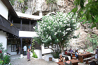 The court yard with cafe restaurant. The source of the Buna river and the house of the Whirling Dervishes, an old Muslim monastery, Blagaj. Federation Bosne i Hercegovine. Bosnia Herzegovina, Europe.