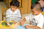 Preschool 3-4 year olds art activity two boys drawing with markers using opposite hands