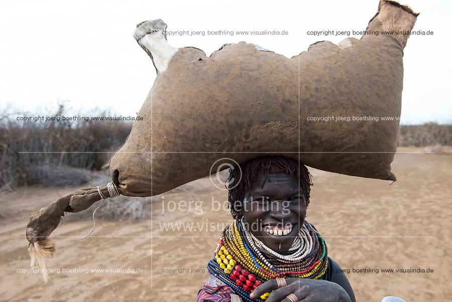 ETHIOPIA, Southern Nations, Lower Omo valley, Kangaten, village Kakuta, Nyangatom tribe, woman with water in leather bag / AETHIOPIEN, Omo Tal, Kangaten, Dorf Kakuta, Nyangatom Hirtenvolk, Frau traegt einen Wassersack aus Tierhaut