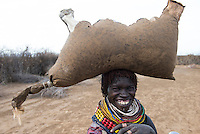 ETHIOPIA, Southern Nations, Lower Omo valley, Kangaten, village Kakuta, Nyangatom tribe, woman with water in leather bag / AETHIOPIEN, Omo Tal, Kangaten, Dorf Kakuta, Nyangatom Hirtenvolk, Frau traegt einen Wassersack aus Tierhaut