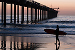 La Jolla, California; a surfer stands with her surf board at the water's edge waiting for her friend to exit the water just after sunset, next to Scripps Pier