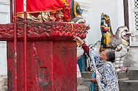 Nepal, Kathmandu.  Woman Making a Candle Offering to Hanuman Statue, Durbar Square.