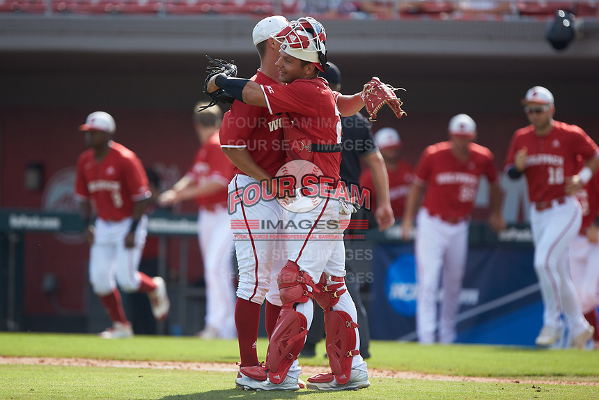 North Carolina State Wolfpack catcher Jack Conley (23) hugs relief pitcher Nolan Clenney (39) following the win over the Army Black Knights at Doak Field at Dail Park on June 3, 2018 in Raleigh, North Carolina. The Wolfpack defeated the Black Knights 11-1. (Brian Westerholt/Four Seam Images)