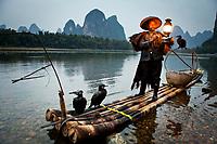 China, Guangxi Zhuangzu Zizhiqu, Guangxi, Yangshuo, Cormorant fisherman with karst mountains and Li River in the background
