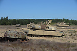 "American M1A2 Abrams tanks beside a damaged old Russian C-55 during a tank maneuver training exercise where Americans and Danes worked together to simulate battle against opposing forces at the Drawsko Pomorskie Training Area in Poland on June 11, 2015.  NATO is engaged in a multilateral training exercise ""Saber Strike,"" the first time Poland has hosted such war games, involving the militaries of Canada, Denmark, Germany, Poland, and the United States."