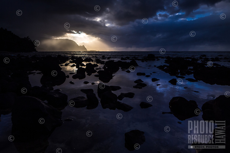 A moody sky of clouds, rain and evening light at Hideaways Beach in Princeville, Kaua'i.