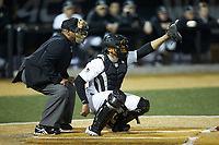 Wake Forest Demon Deacons catcher Christian Long (19) reaches for a high pitch as home plate umpire Gregory Street looks on during the game against the Sacred Heart Pioneers at David F. Couch Ballpark on February 15, 2019 in  Winston-Salem, North Carolina.  The Demon Deacons defeated the Pioneers 14-1. (Brian Westerholt/Four Seam Images)
