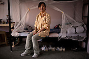 25 year old Chinese interpreter, Li Wez Wez poses for a portrait in her dormitory  in the Chinese Colony of the Adani Power Plant in Mundra port industrial city of Gujarat, India. Indian power companies have handed out dozens of major contracts to Chinese firms since 2008. Adani Power Ltd have built elaborate Chinatowns to accommodate Chinese workers, complete with Chinese chefs, ping pong tables and Chinese television. Chinese companies now supply equipment for about 25% of the 80,000 megawatts in new capacity.