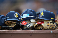 North Carolina A&T Aggies caps rest on gloves on top of the visitors dugout during the game against the North Carolina Central Eagles at Durham Athletic Park on April 10, 2021 in Durham, North Carolina. (Brian Westerholt/Four Seam Images)