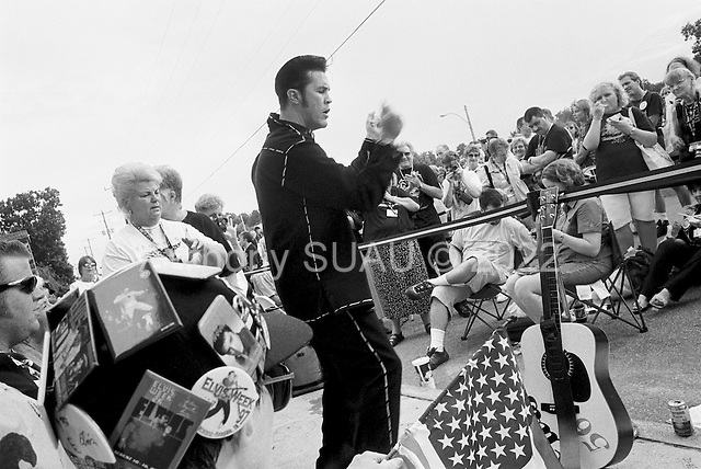 "Memphis, Tennessee<br /> USA<br /> August 15, 2002<br /> <br /> An Elvis impersonator performing ""Jail House Rock"" before some 50, 000 Elvis fans from around the world gathered outside of Graceland for a candle vigil to mark the 25th anniversary of Elvis Presley's death."