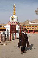A Tibetan man outside the Upper Wutan Monastery, Rebgong (Chinese name - Tongren),  on the Qinghai-Tibetan Plateau. China.