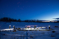Teams rest on the river as dusk falls on the halfway checkpoint of Iditarod on Thursday March 7, 2013...Iditarod Sled Dog Race 2013..Photo by Jeff Schultz copyright 2013 DO NOT REPRODUCE WITHOUT PERMISSION