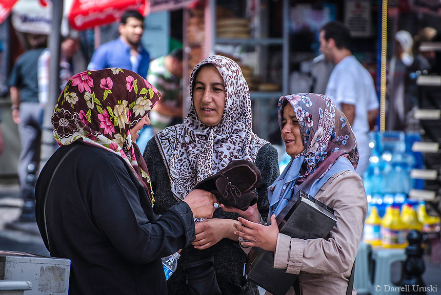 Urban Street Photography. A busy marketplace in Istanbul, Turkey. Three Turkish women wearing their traditional headscarves are outside a shop discussing their purchase of footwear.