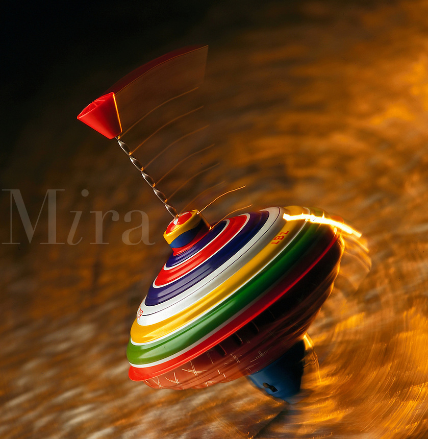 Streaked, brightly colored spinning toy top in motion on fiery background.