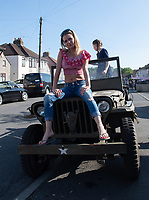 A young lady poses on a WW2 Jeep at a street  party in Welling, Kent, England 8th May 2020. Victory in Europe (VE) 75th Anniversary Celebrations during the UK Lockdown due to the Coronavirus pandemic. Photo by Alan Stanford / PRiME Media Images