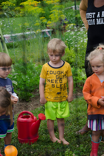 """Young boy in garden camp with great T-shirt """"tough guys need sleep too"""", Yarmouth Community Garden, Maine, USA"""