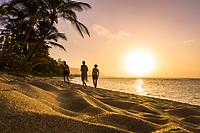 At sunset, people walk the shore at Mokule'ia Beach near Crozier Drive, North Shore, O'ahu.
