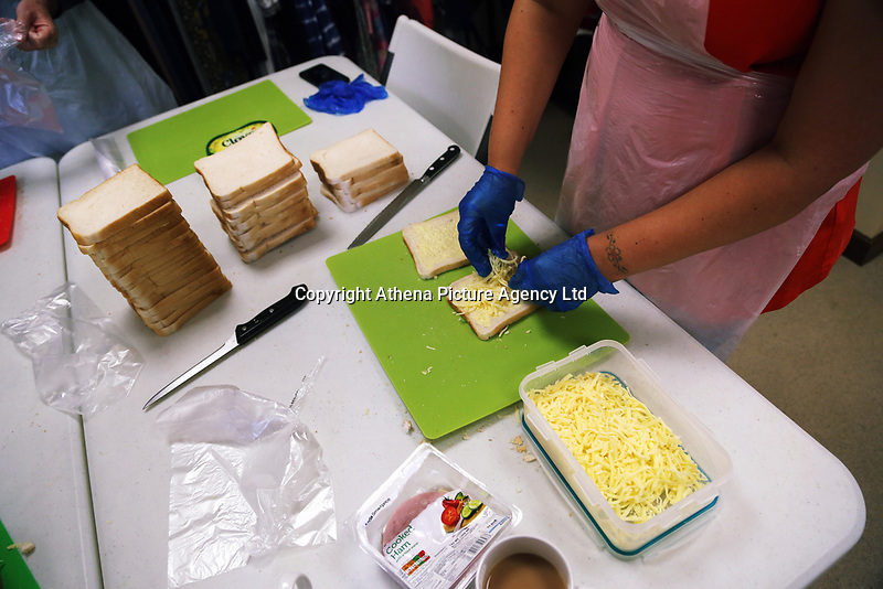 Pictured: A volunteer prepares cheese sandwiches at Jersey Park Pavilion in Swansea, UK. Friday 25 August 2017<br /> Re: Free food for children story, Swansea, Wales, UK.