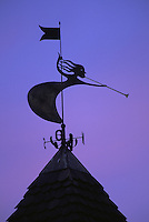 Weathervane figure of girl playing horn silhouetted against dusk sky, Castelrotto (Kastelruth), Italy