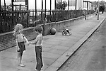 Children playing together in the street, south London prefab housing behind them. England 1970s..They are playing Make Up Make Up Never Do it Again.