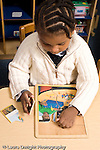 Educaton preschool 4-5 year olds girl playing with wooden puzzle vertical