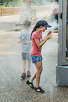 Kids cool off with the help of a refreshing mist machine at a park.