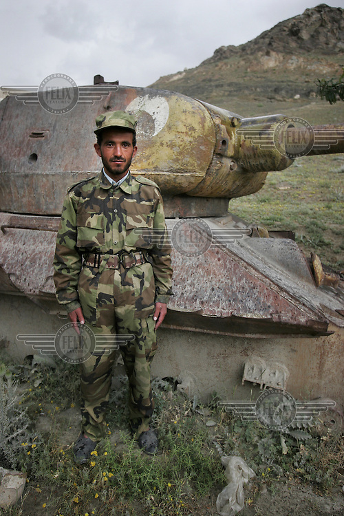 A soldier with the Afghan National Army (ANA) poses in front of an old Soviet tank. Kabul, Afghanistan.