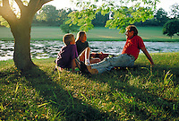 Father talks with son about 9 years old and daughter about 12 years old in park beside lake. father and children. Harrisburg Pennsylvania United States Park.