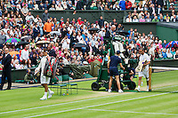 02-07-12, England, London, Tennis , Wimbledon,          Xavier Malisse  and  Roger Federer(L) leaving the court when rain sets in.