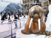 Switzerland. Canton Ticino. Lugano. Piazza Riforma. A skating rink with families and a walrus standing on a fake artic scenery. The walrus (Odobenus rosmarus) is a large flippered marine mammal. 24.12.12 © 2012 Didier Ruef