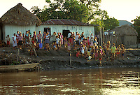 Villagers gather at the bank of the Magdalena River located in the interior of Colombia, South America to greet visitors. waterways, travel, tourism. Villagers on Magdalena River. Colombia village along Magdalena River.