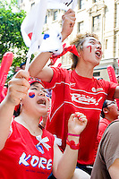 """South Korea fans Jung Wong, left, and Kun Cho watch their team play against France on June 18, 2006 on a giant outdoor television in a section of New York City known as """"Korea Way""""...The World Cup, held every four years in different locales, is the world's pre-eminent sports tournament in the world's most popular sport, soccer (or football, as most of the world calls it).  Qualification for the World Cup is open to any country with a national team accredited by FIFA, world soccer's governing body. The first World Cup, organized by FIFA in response to the popularity of the first Olympic Games' soccer tournaments, was held in 1930 in Uruguay and was participated in by 13 nations.    ..As of 2010 there are 208 such teams.  The final field of the World Cup is narrowed down to 32 national teams in the three years preceding the tournament, with each region of the world allotted a specific number of spots.  ..The World Cup is the most widely regularly watched event in the world, with soccer teams being a source of national pride.  In most nations, the whole country is at a standstill when their team is playing in the tournament, everyone's eyes glued to their televisions or their ears to the radio, to see if their team will prevail.  While the United States in general is a conspicuous exception to the grip of World Cup fever there is one city that is a rather large exception to that rule.  In New York City, the most diverse city in a nation of immigrants, the melting pot that is America is on full display as fans of all nations gather in all possible venues to watch their teams and celebrate where they have come from. ."""