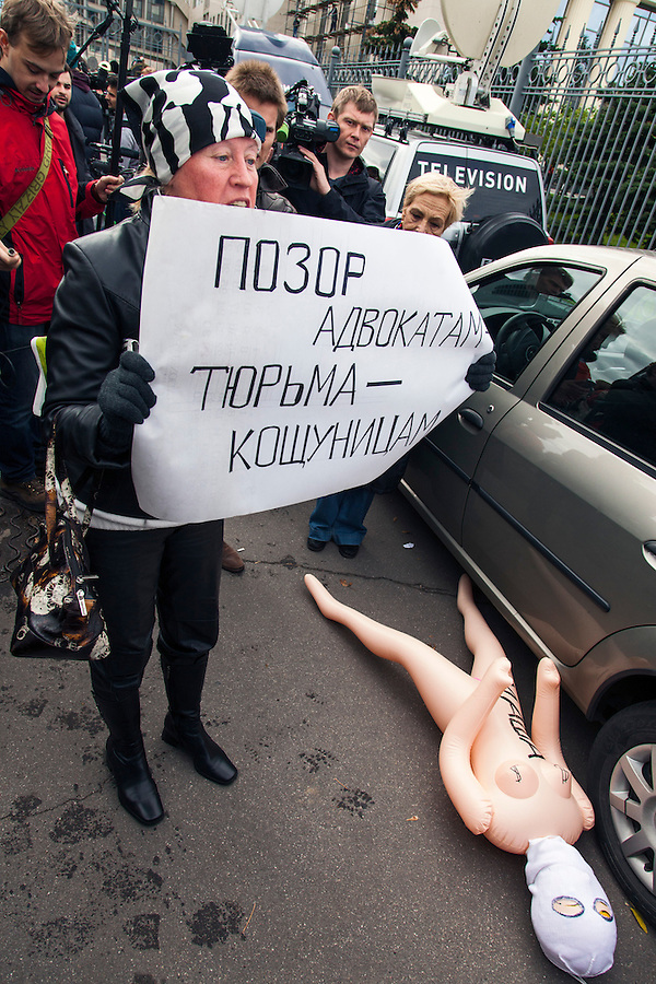 Moscow, Russia, 01/10/2012..An anti Pussy Riot protester stands beside an inflatable sex dolls with the names of Pussy Riot members outside Moscow City Court. Supporters and opponents of band members Maria Alyokhina, Yekaterina Samutsevich and Nadezhda Tolokonnikova demonstrated outside the court as the three appealed against their two-year jail sentence for their performance in the Christ The Saviour Cathedral. The appeal was postponed until October 10th after Samutsevich fired her lawyer.