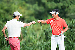 Xing Aowei (pink pants) and Man Wenjun (orange shirt) at the end of their game during the World Celebrity Pro-Am 2016 Mission Hills China Golf Tournament on 23 October 2016, in Haikou, Hainan province, China. Photo by Weixiang Lim / Power Sport Images