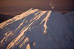 Sunset reflects off the snowy southwetern slopes of Mount St. Helens, Washington
