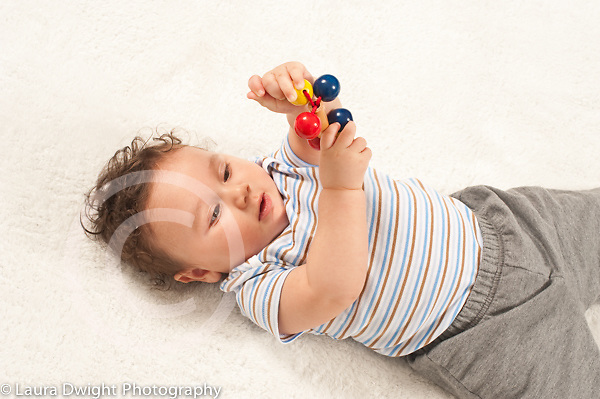 6 month old baby boy closeup on back using both hands to hold and move wooden toy with colorful wood balls attached by strings