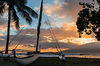 Sunset over a Hawaiian sailing canoe on a beach in Lahaina, Maui, with Lana'i in the distance.