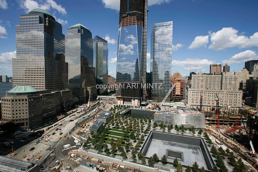 Tenth anniversary of 9/11.  Rebuilding at the World Trade Center site.  The view from south side of site shows L to R: World Financial Center buildings, Goldman Sachs, 1 WTC, 7 WTC, and the postal building.   The 9/11 Memorial is situated around the footprints of the original towers.   Photo by Ari Mintz.  8/22/2011.