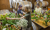 Flower arranging, Evie wedding in wine storage room at Pacheco Ranch Winery