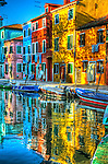 Colourful houses on a quiet canal on the island of Burano, Venice, Italy.