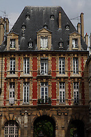 Paris Right Bank: The ancient building at the entrance from rue de Bretagne of place des Vosges (XVII century), in the Marais, with its three arcs, its red bricks, and its particular roof in slate. This is the Pavillon du Roi (the Pavillon of the King), on the background of a grey sky.<br /> <br /> You can download this file for (E&PU) only, but you can find in the collection the same one available instead for (Adv).