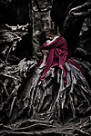 Beautiful young woman in a red dress curled up like a baby inside the root system of an old dead tree in a forest Image © MaximImages, License at https://www.maximimages.com