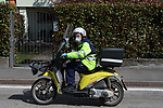 24/03/2020 in Pergine Valsugana, Italy. Most part of Europe is today on a sweeping confinement to try to slow down the spread of the Covid-19 Pandemic. A postman on his scooter wearing gloves and mask.