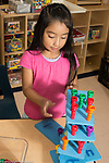 Education Preschool 4 year olds girl stacking number peg boards on top of each other