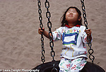 Girl  3 years old outside: playgroung: happy in tire swing